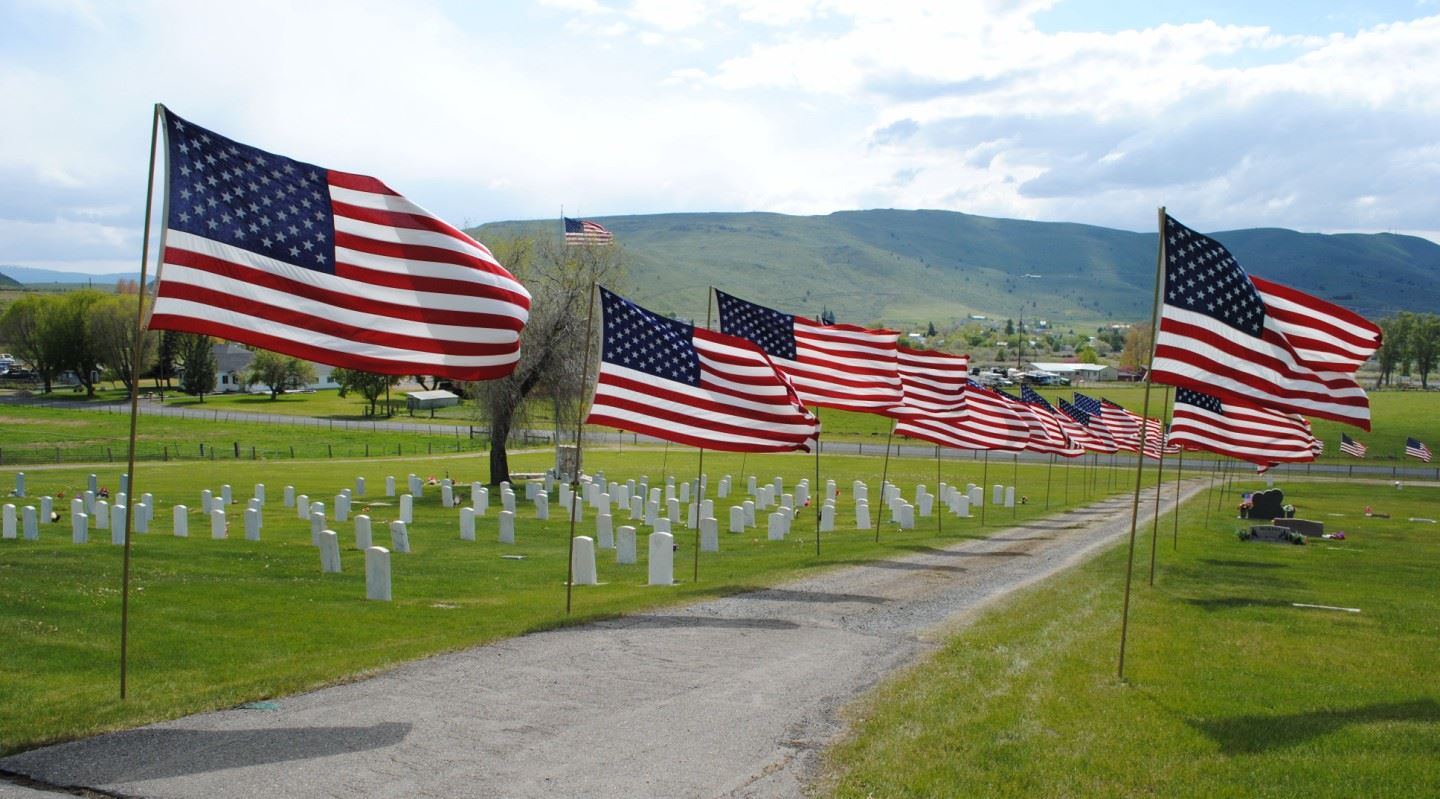 Flags lining the driveway of the cemetery